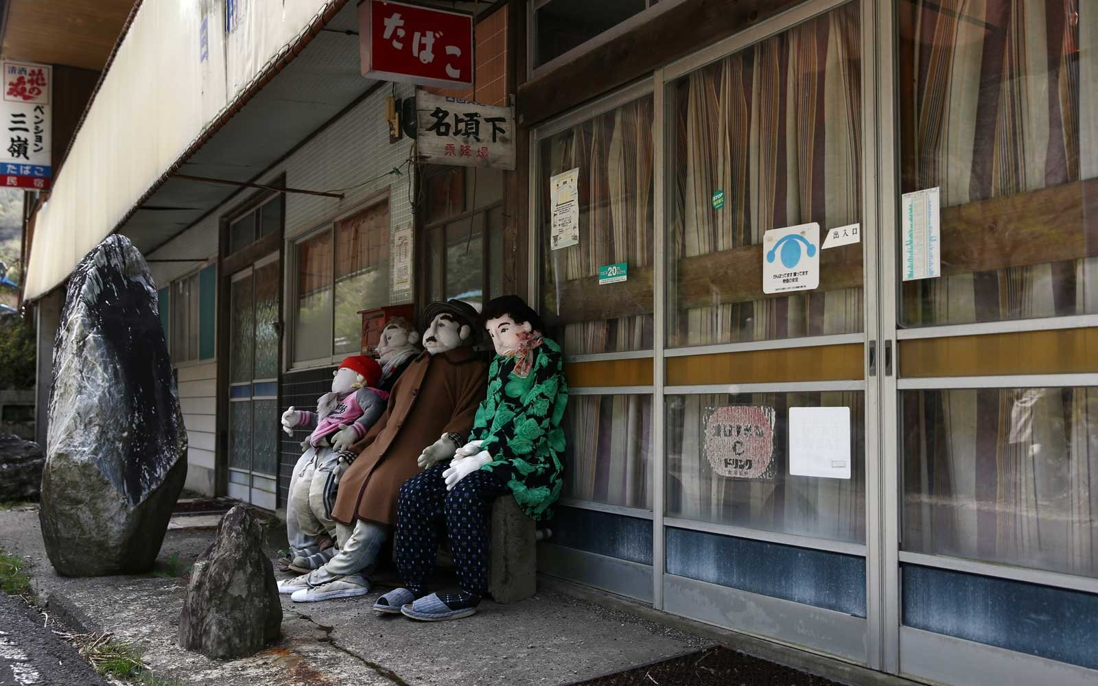 Hand-made dolls are seated outside a closed-down shop as others are placed around the village by local resident Tsukimi Ayano to replace the dwindling local population in Nagoro village, in Miyoshi, Japan