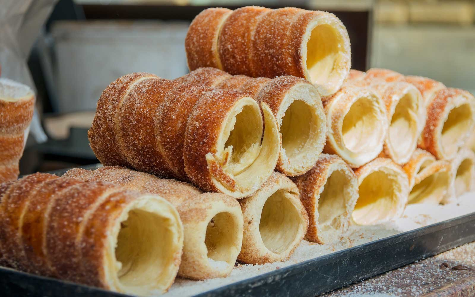 Chimney cakes are baked over a fire to caramelize and are topped with cinnamon and sometimes nuts.