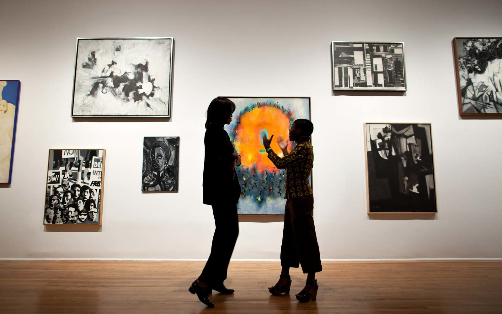 Michelle Obama talks with Director and Chief Curator Thelma Golden during a tour of the Studio Museum in Harlem