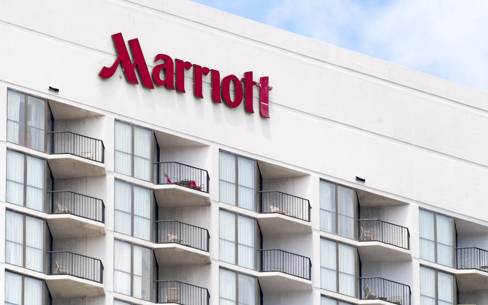 Marriott hotel sign in a downtown building, red metal lettering placed vertically on round building facade.