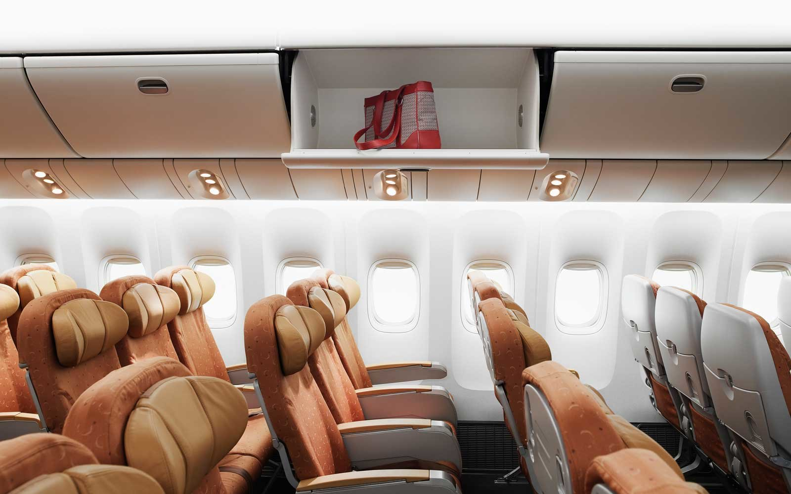 Empty airplane interior, bag left in overhead bin, side view