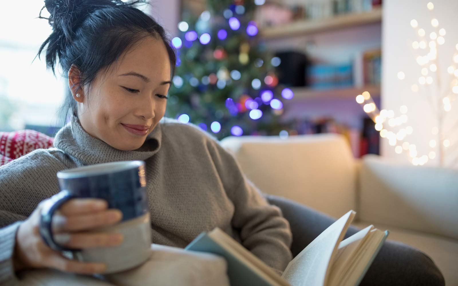 Smiling woman drinking coffee and reading book in Christmas living room