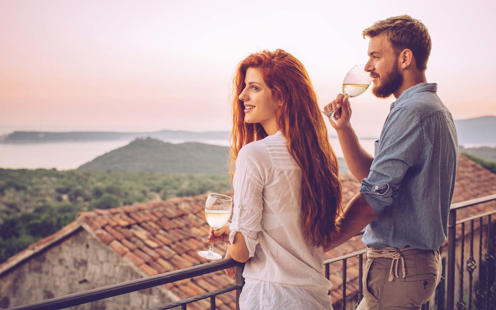 Young couple drinking wine on balcony at their holiday tourist resort