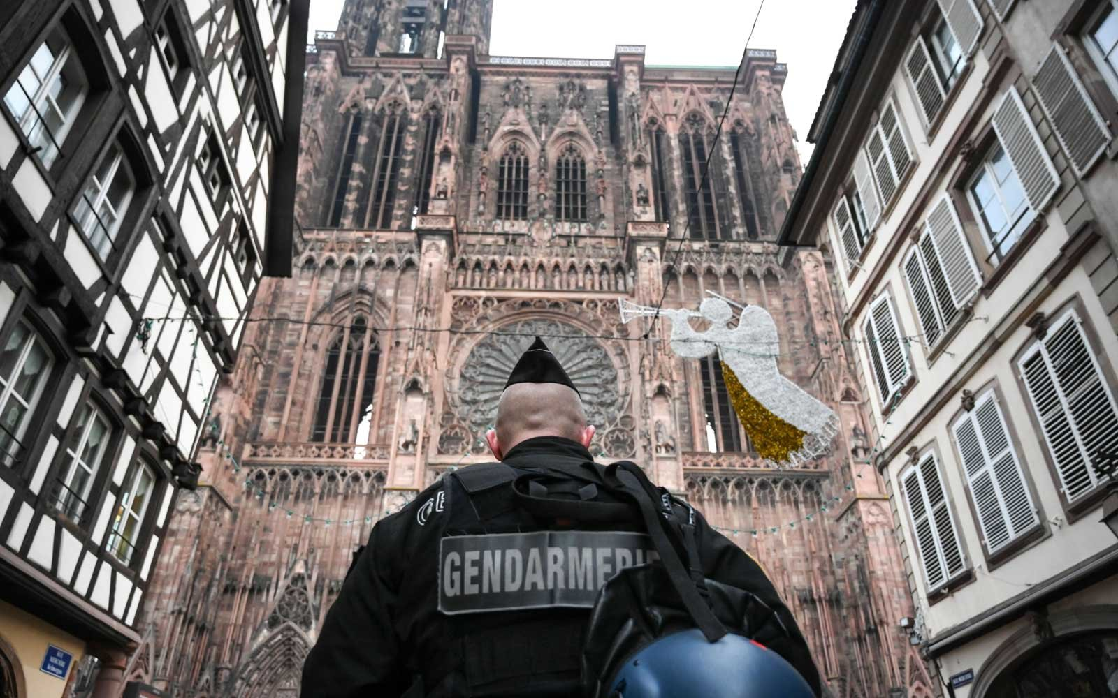 A French gendarme patrols in front of the Strasbourg cathedral while searches are conducted on December 12, 2018