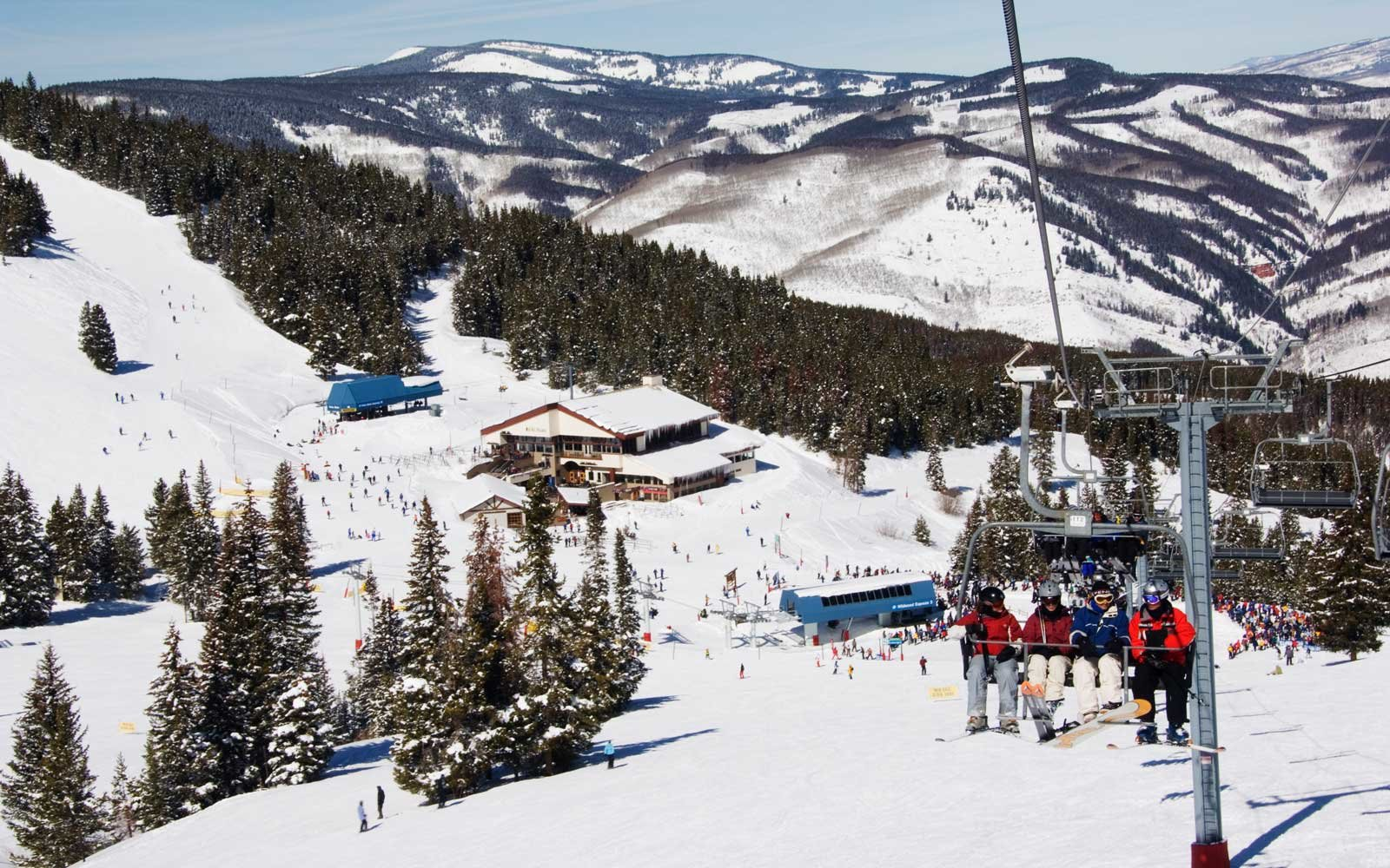 Skiers being carried on a chair lift to the back bowls of Vail ski resort, Vail, Colorado