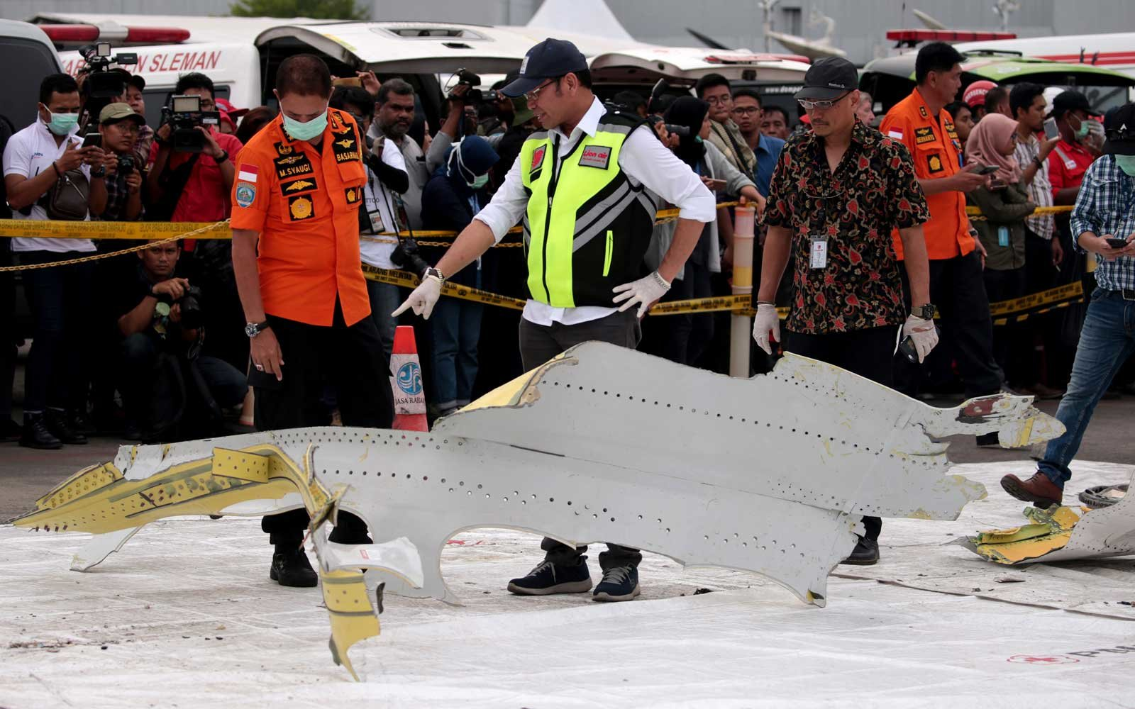 The Indonesian National Transportation Safety Committee (KNKT) members and the Indonesian National Board for Disaster Management (BNPB) members check ruins of the crashed Lion Air flight JT610 during their investigation  at Tanjung Priok port in Jakarta