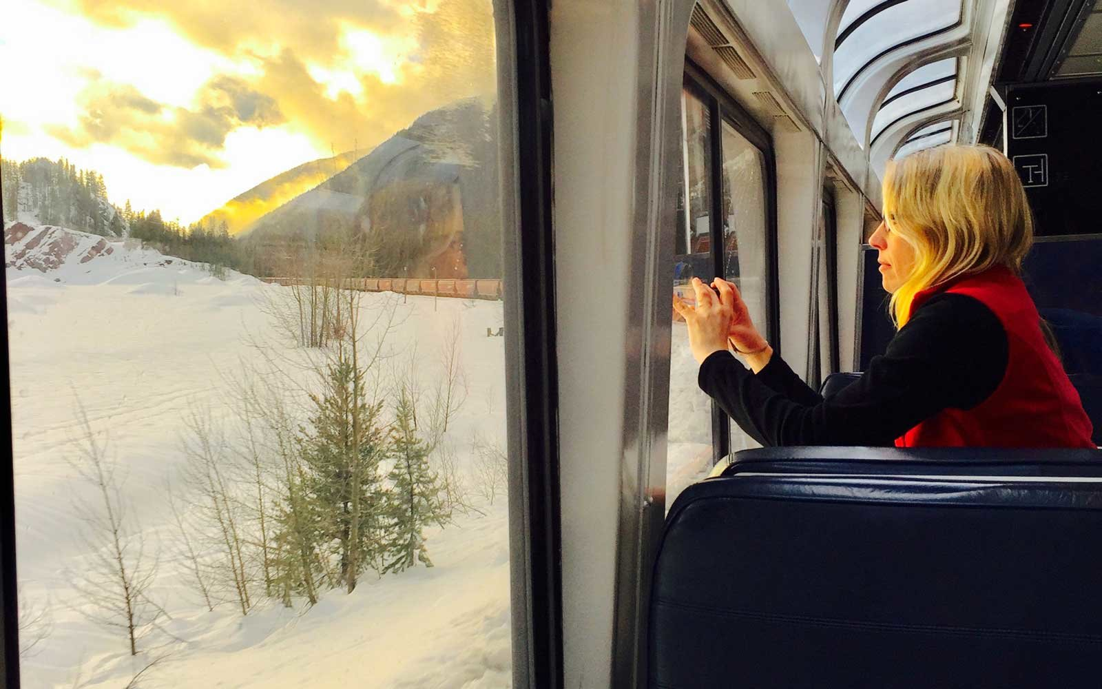 Passenger taking photo from Amtrak Empire Builder train of Glacier National Park