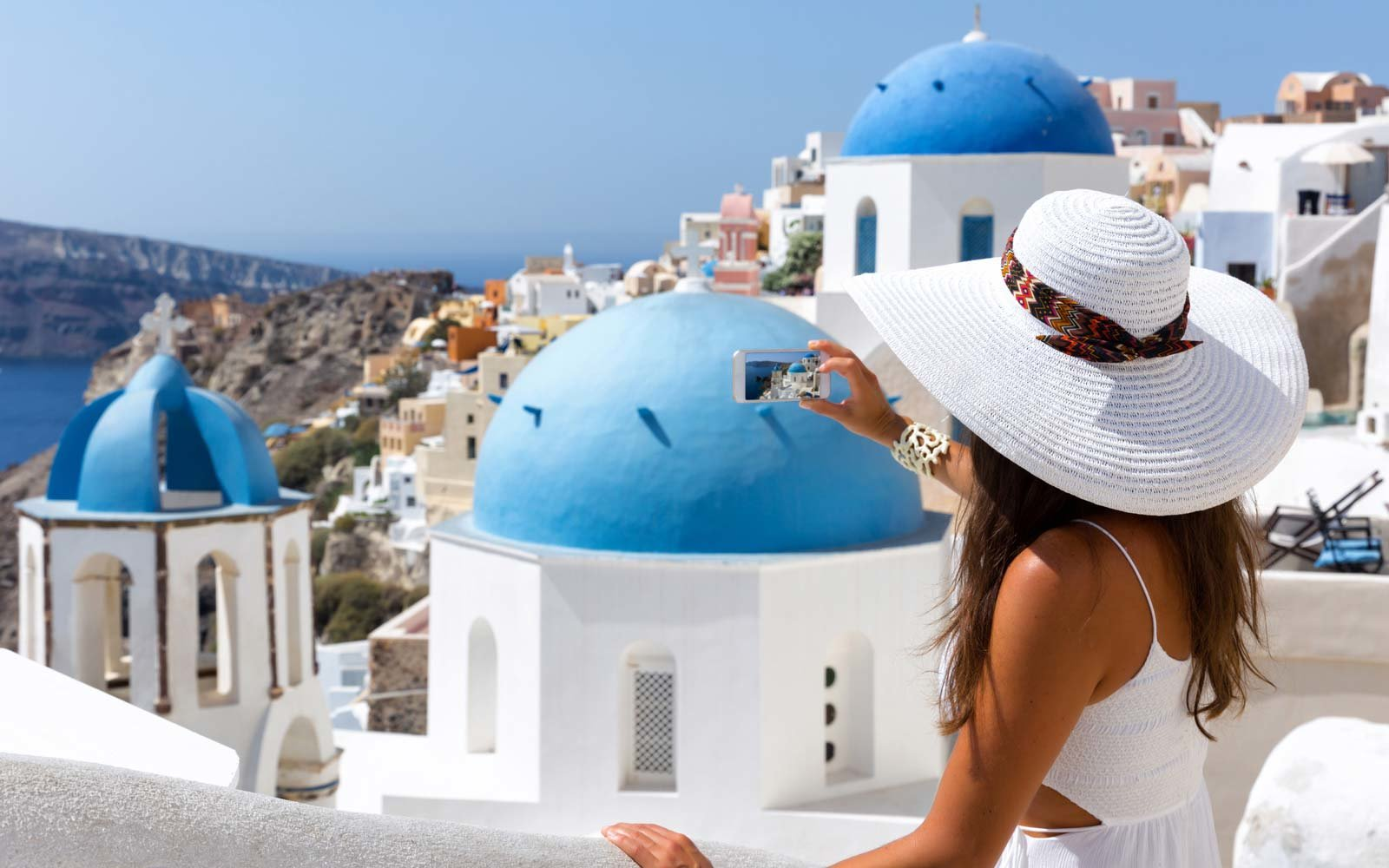 Woman is taking photos in Oia, Santorini