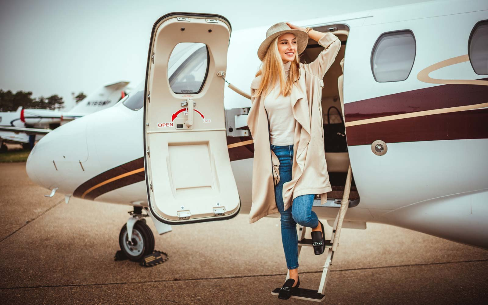 Young elegant rich woman exiting a private jet parked on a runway