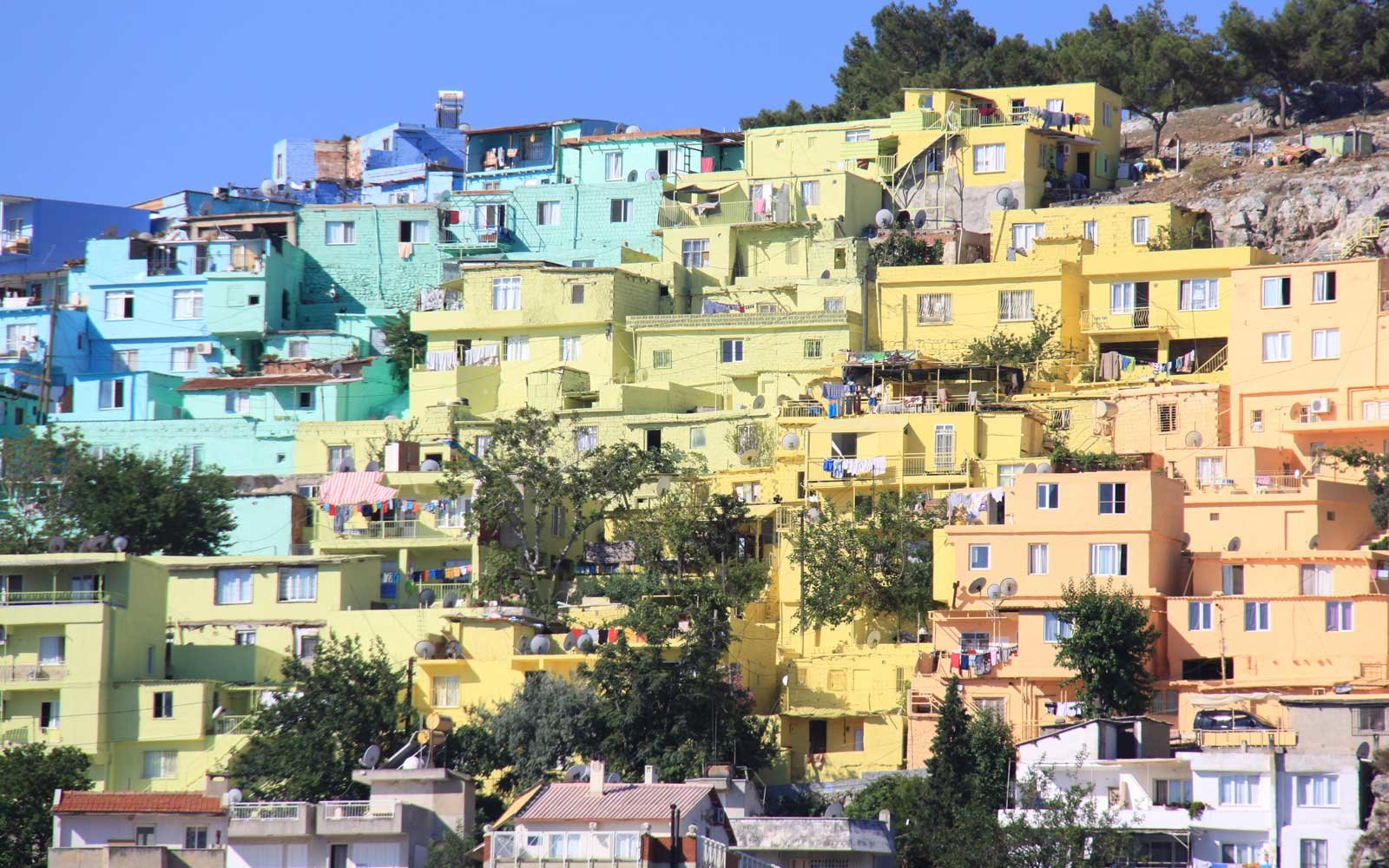 Multi-coloured painted houses on the hillside overlooking the town and port at Kusadasi, Aydin Province, TURKEY