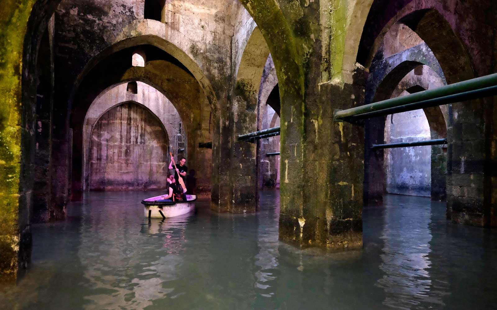 Visitors boating inside the Pool of Arches also known as St. Helen's pool an underground water cictern built in 789 AD in the city of Ramle or Ramla in Israel