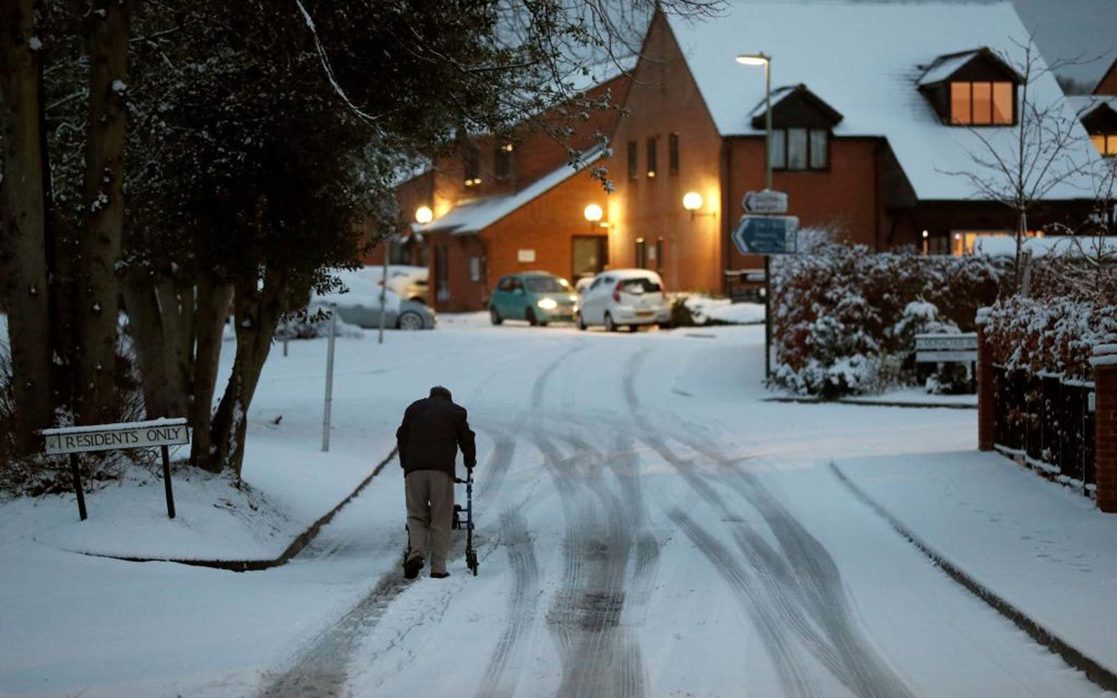 An elderly resident makes his way up a snow covered road in Hartley Wintney, in Hampshire, 40 miles west of London