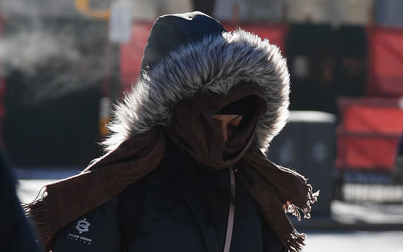 People walk through cold conditions due to the polar vortex.