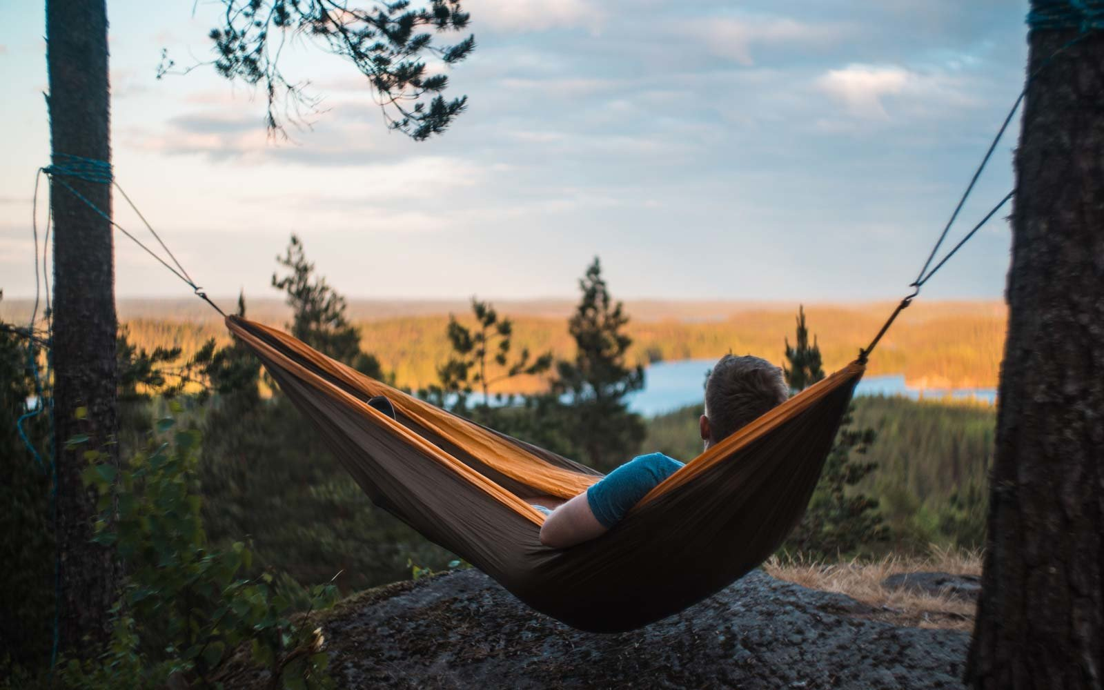 Man Relaxing On Hammock Against Landscape