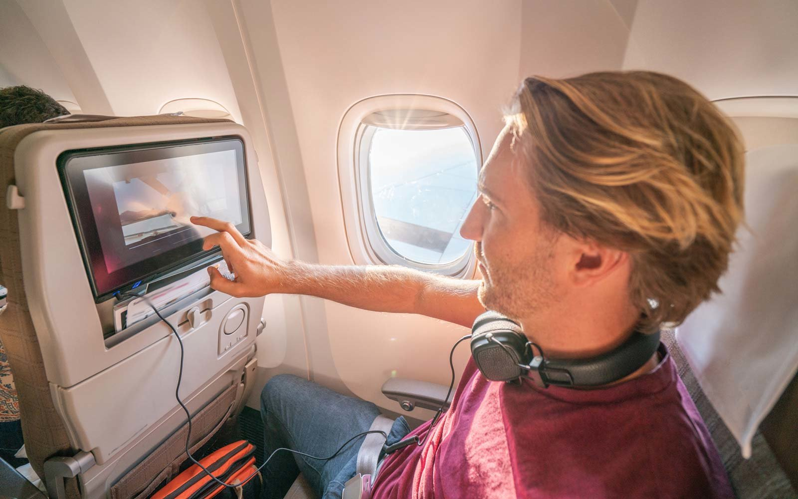 Young man in airplane using onboard entertainment