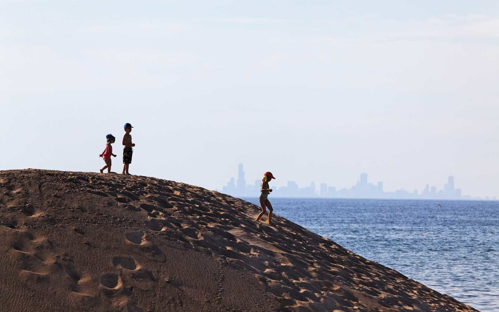 Kids standing on a sand dune in Indiana Dunes National Lakeshore park with skyline of downtown Chicago in the background.