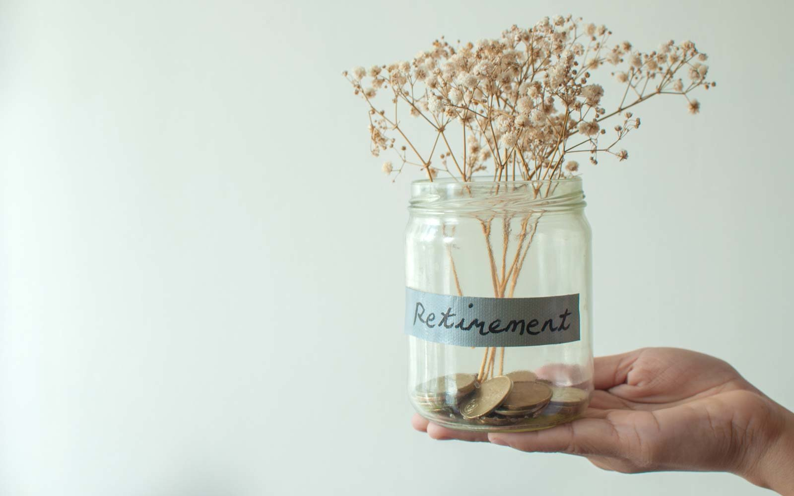 A retirement concept jar with coins and dried plant