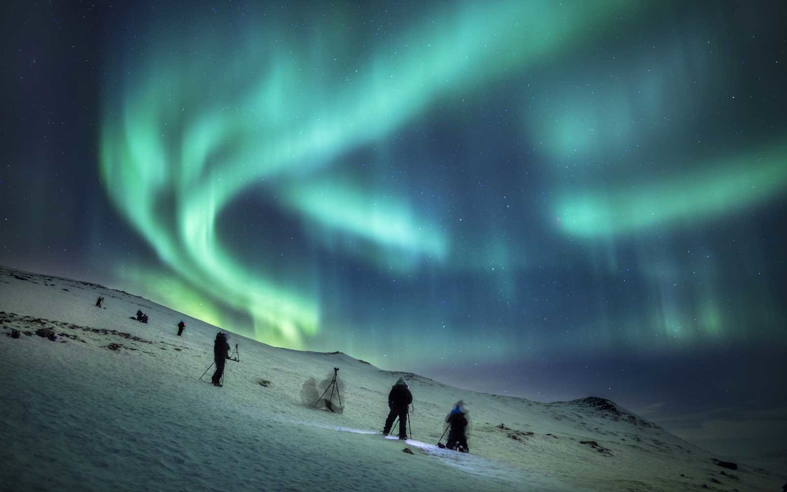 People viewing and photographing the northern lights by the Abisko Sky Station, Lapland, Sweden