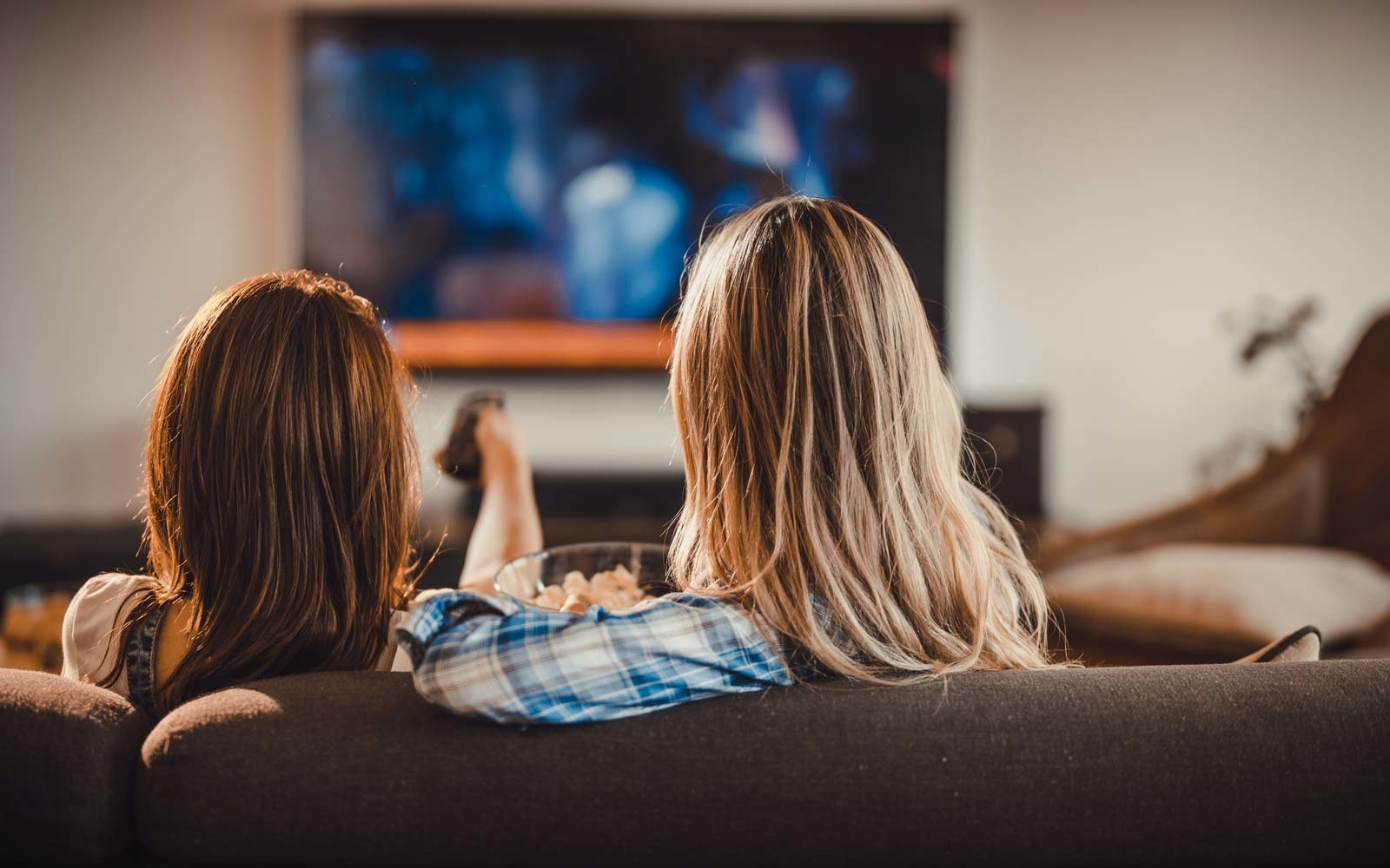 Rear view of two women relaxing on sofa in the living room and watching a movie on TV.