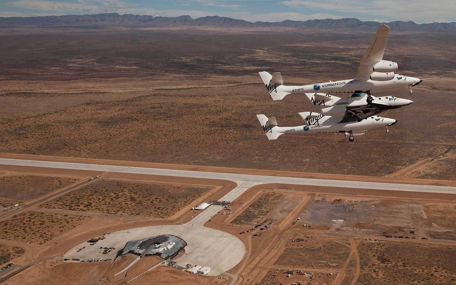 Virgin Galactic vehicles WhiteKnightTwo and SpaceshipTwo fly over Spaceport America