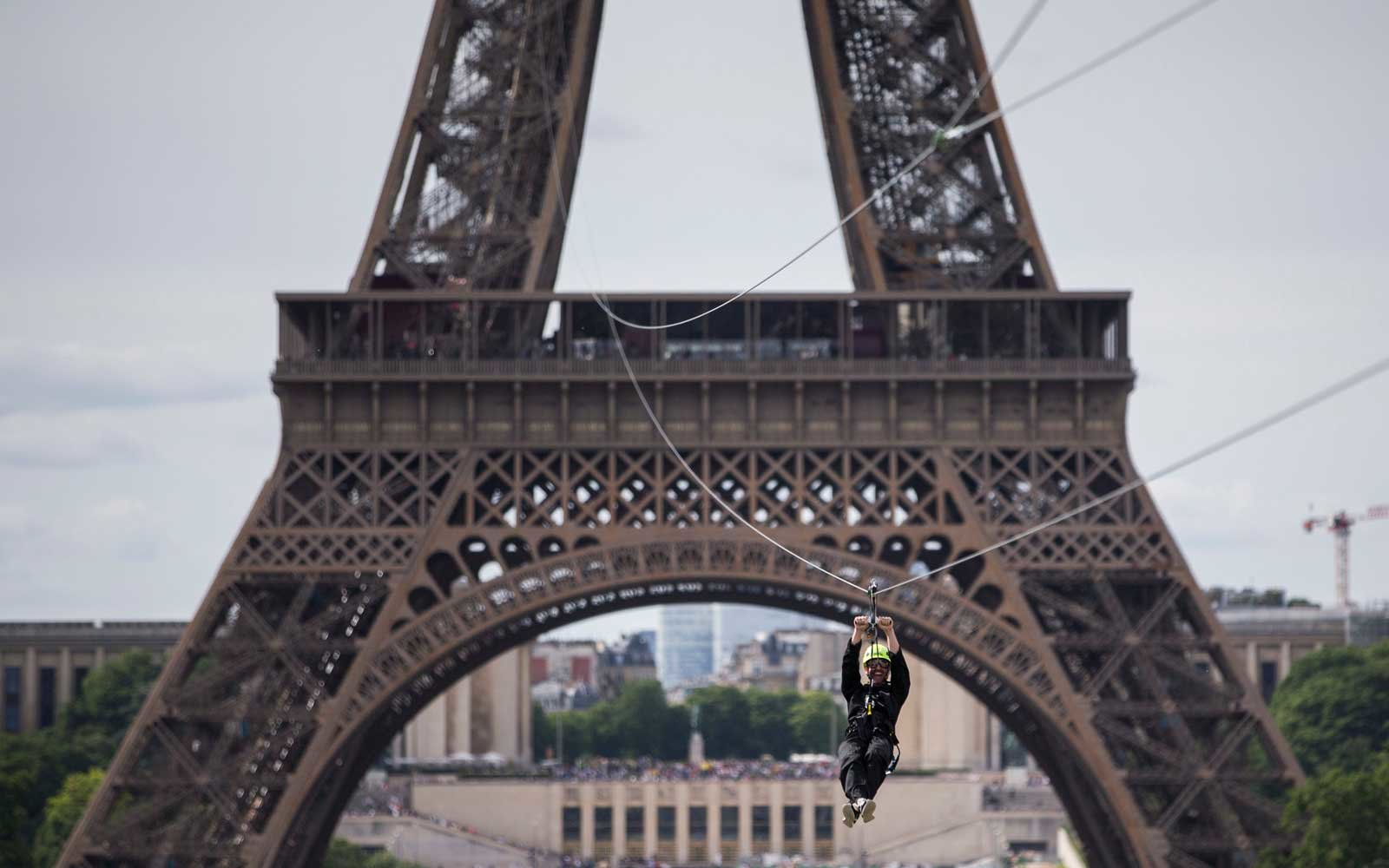 Thrillseekers courageous zip line off Eiffel Tower