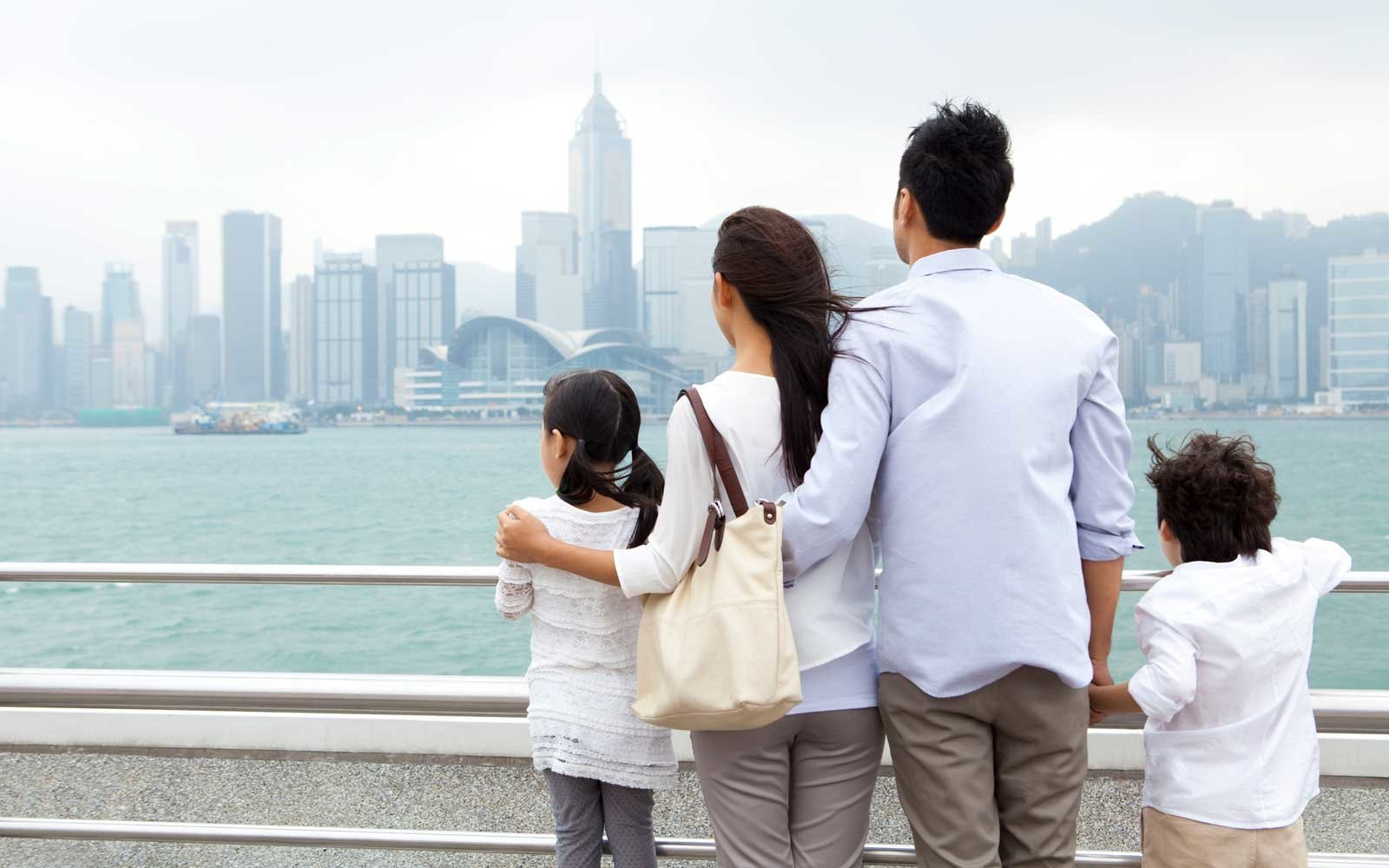 Young family enjoying the beautiful scenery of Victoria Harbor, Hong Kong