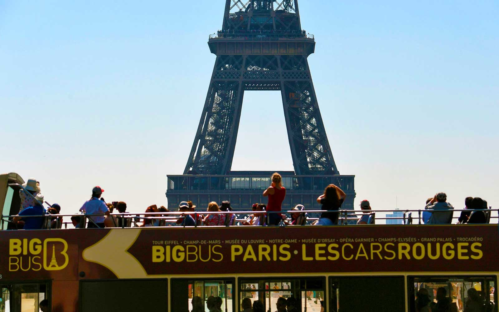 Tourists travel on an opentop bus in front of The Eiffel Tower in Paris
