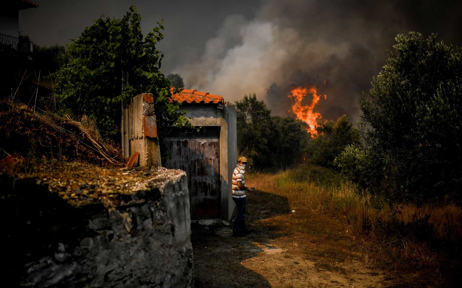 A villager stands near his storage house as a wildfire approaches Roda village in Macao, central Portugal on July 21, 2019.