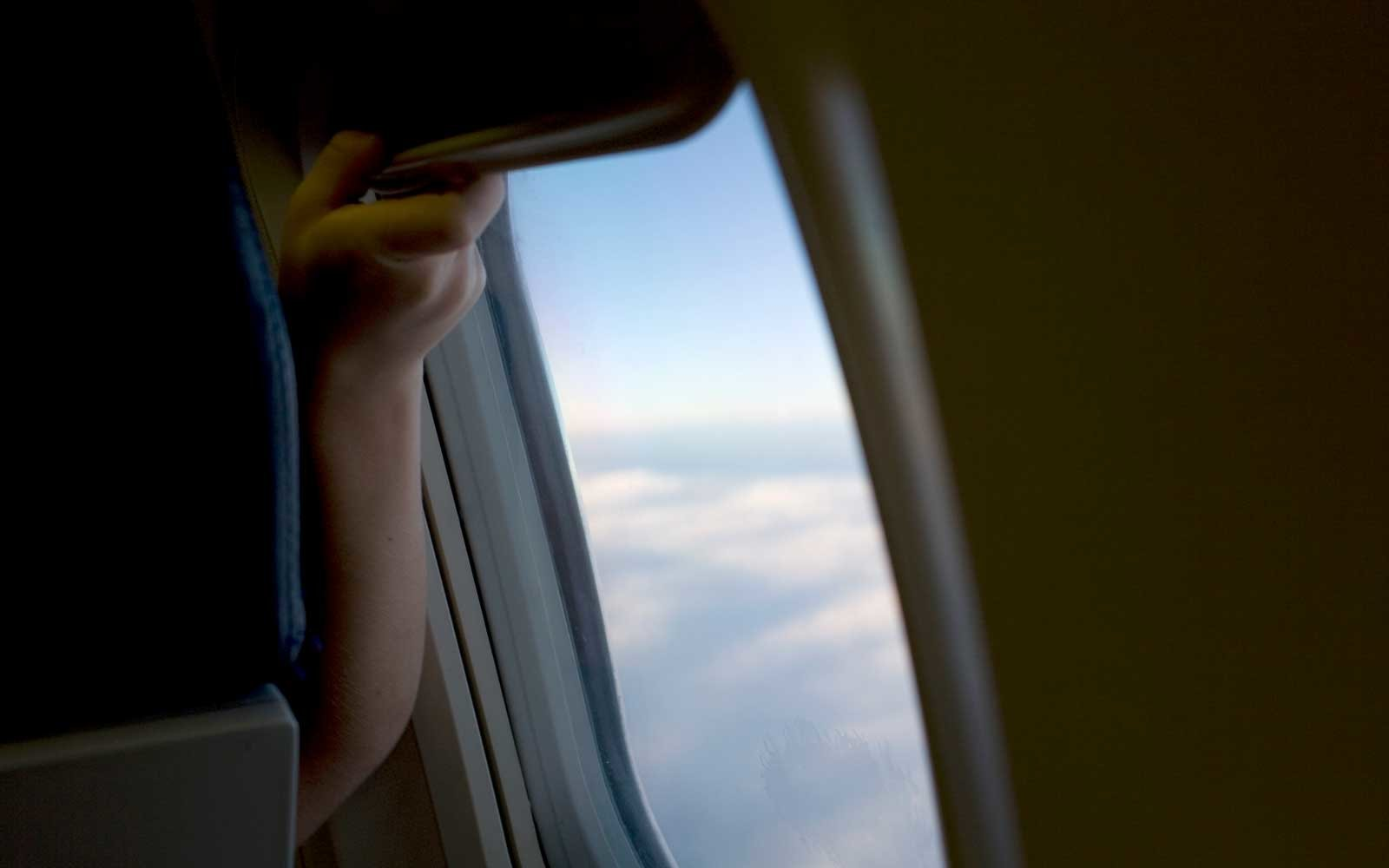 Watch two grown men continuously open and close window shade in ridiculous airplane fight