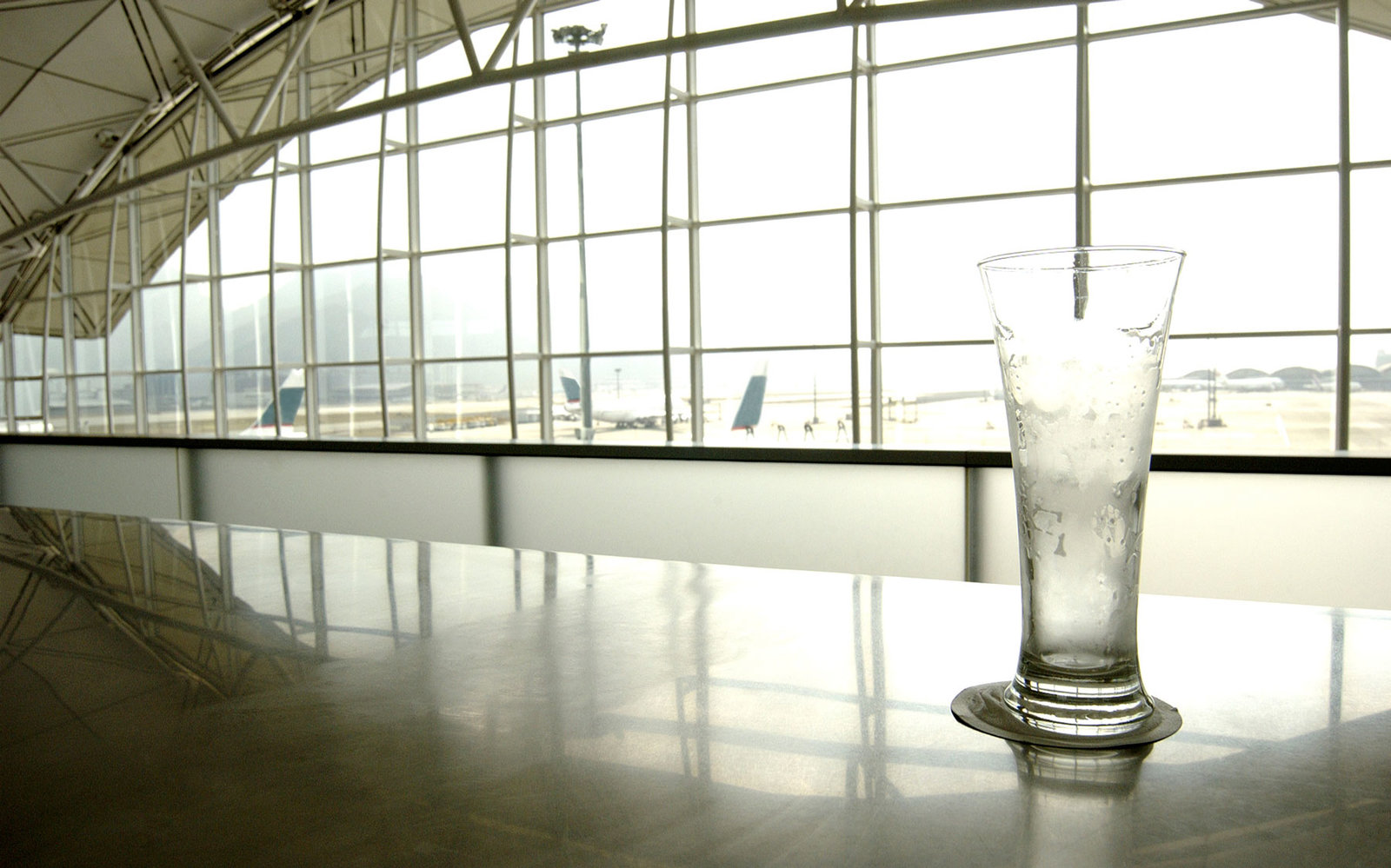 An empty glass sits on a bar at the airport.
