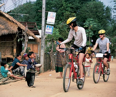 cyclists riding through a village in Thailand