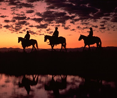 cowboys horseback riding at sunset in Latigo Ranch, Kremmling, CO