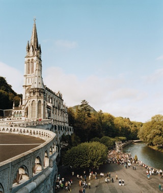 tourists outside the Sanctuary of Our Lady of Lourdes in Lourdes, France