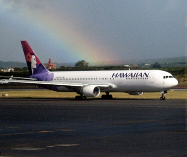 Hawaiian airlines jet on the tarmac with at rainbow behind it