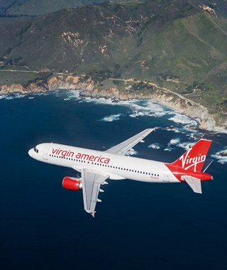 Virgin America airline flying over a coastline