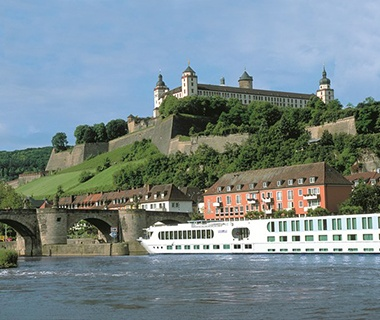 Uniworld cruise ship on the river outside a European castle