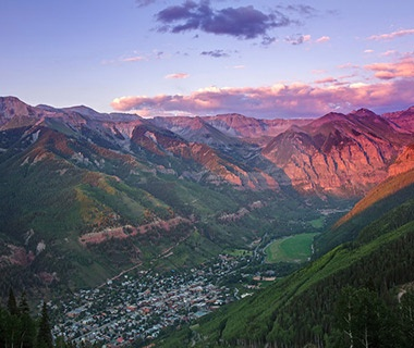 sun setting on the mountains over Telluride town, CO