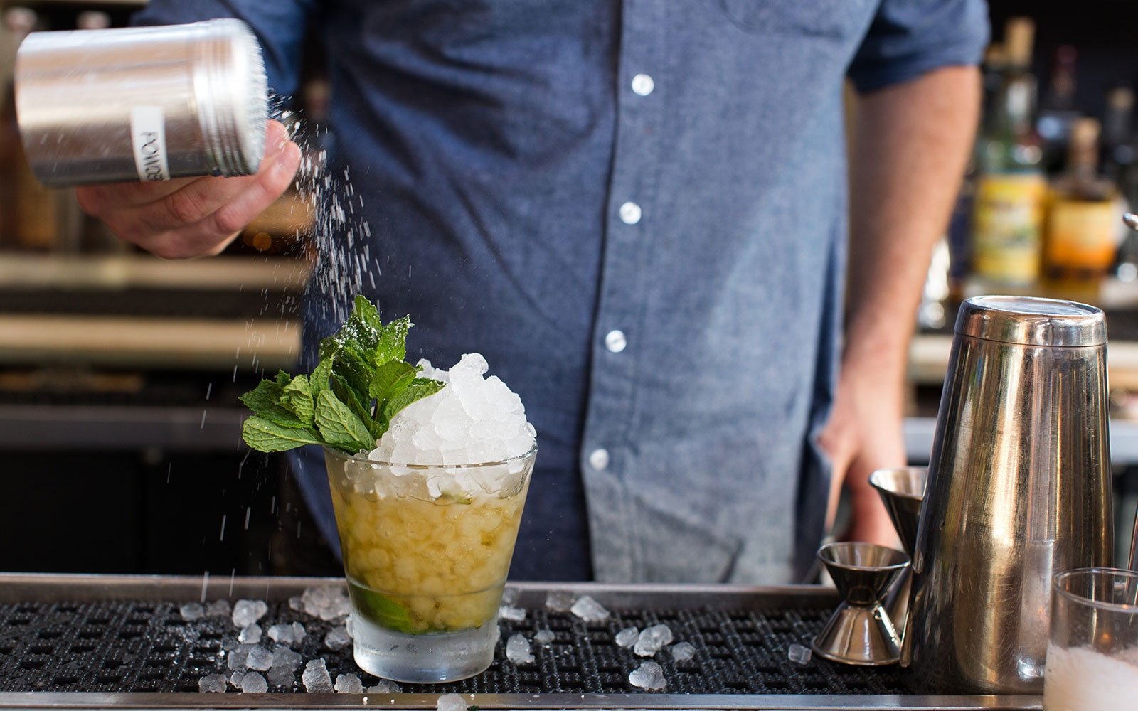 Bartender making mint julep cocktail