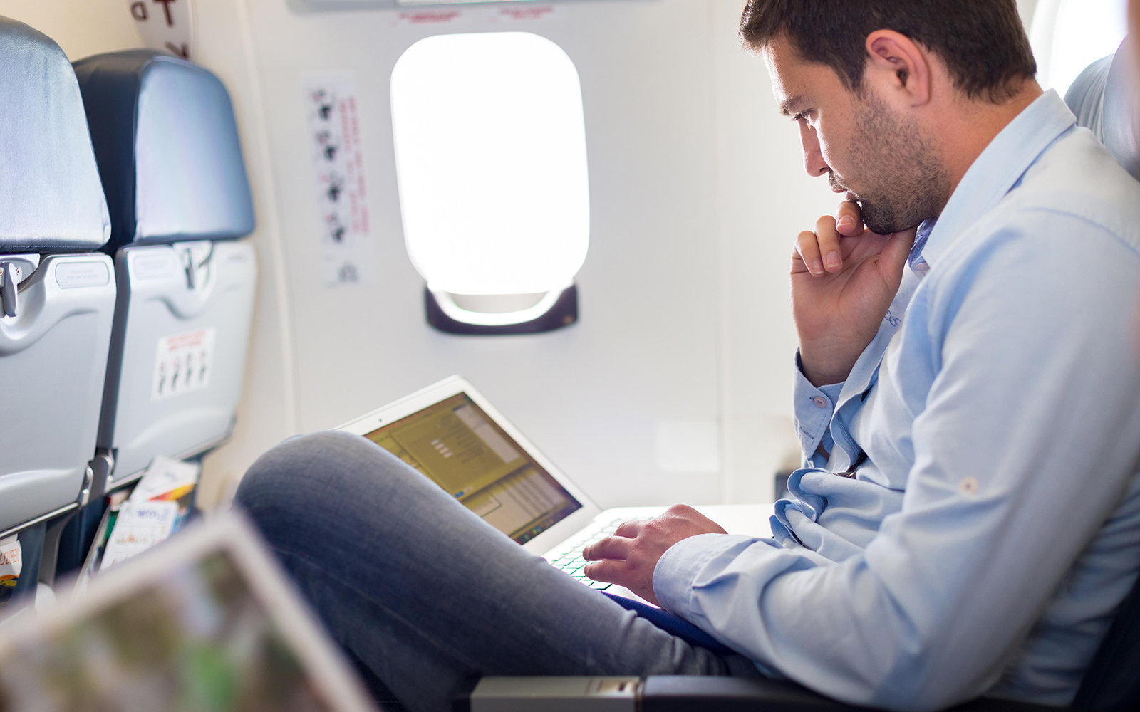Man on laptop in airplane