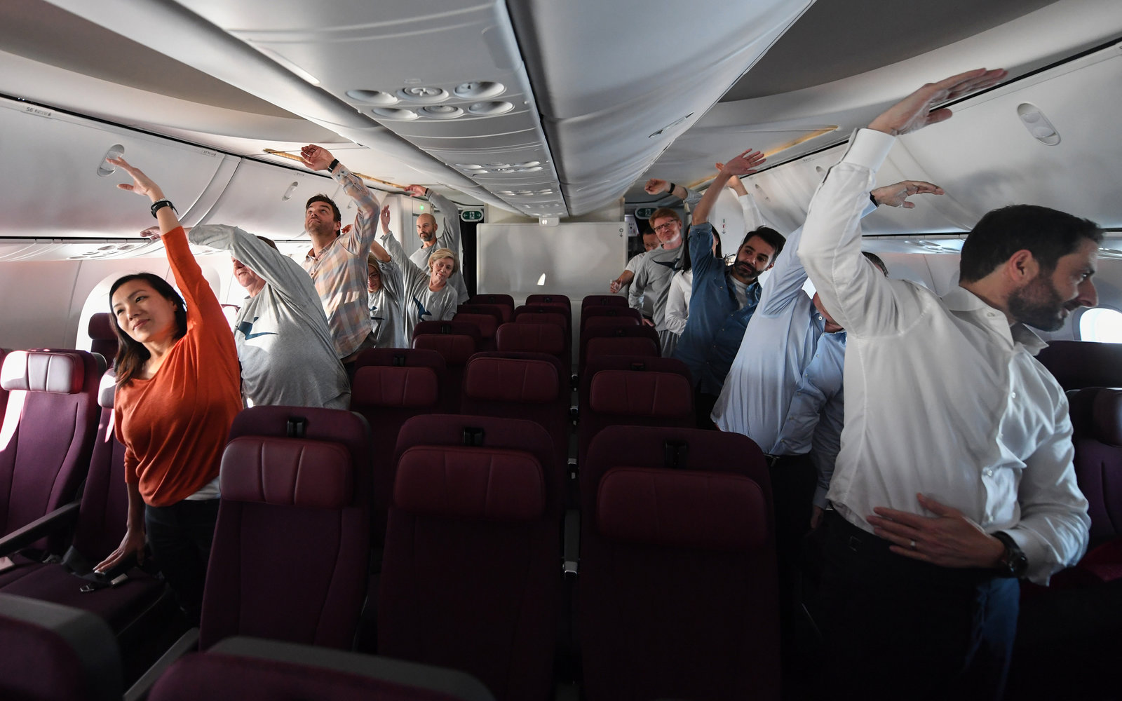 Passengers stretching on a flight from London to Sydney