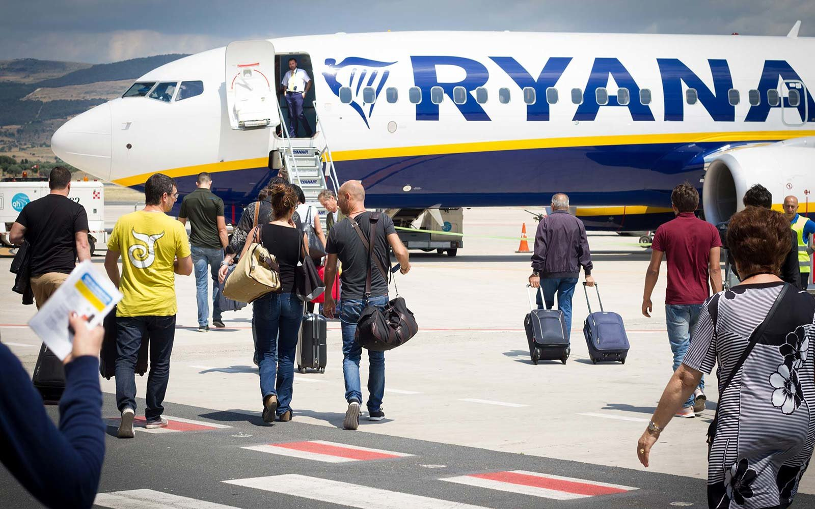 carry-on luggage toward a Ryanair airplane