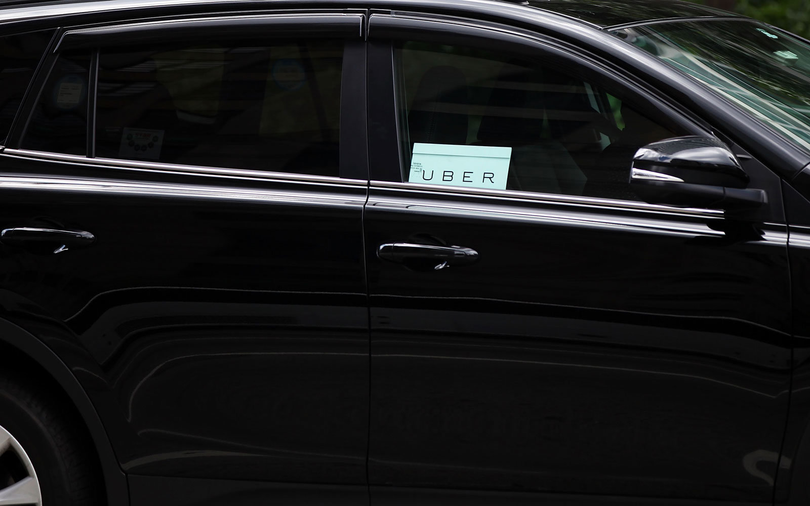 An Uber sign in a car window.