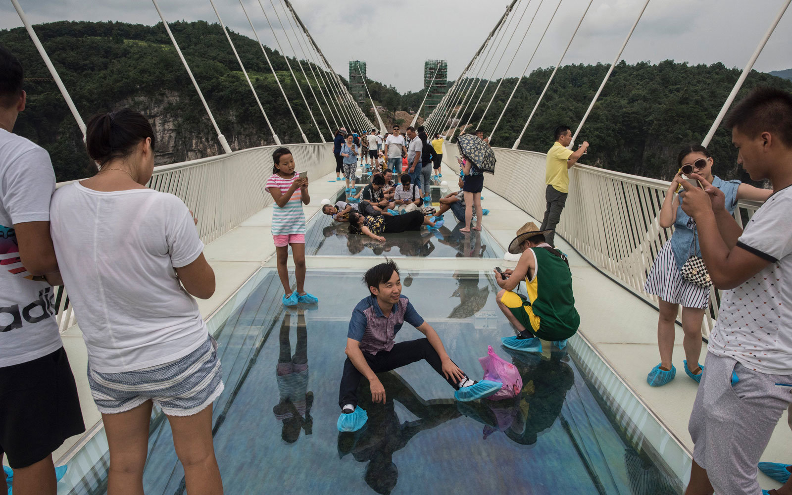 Tourists sit on the glass bridge in China.