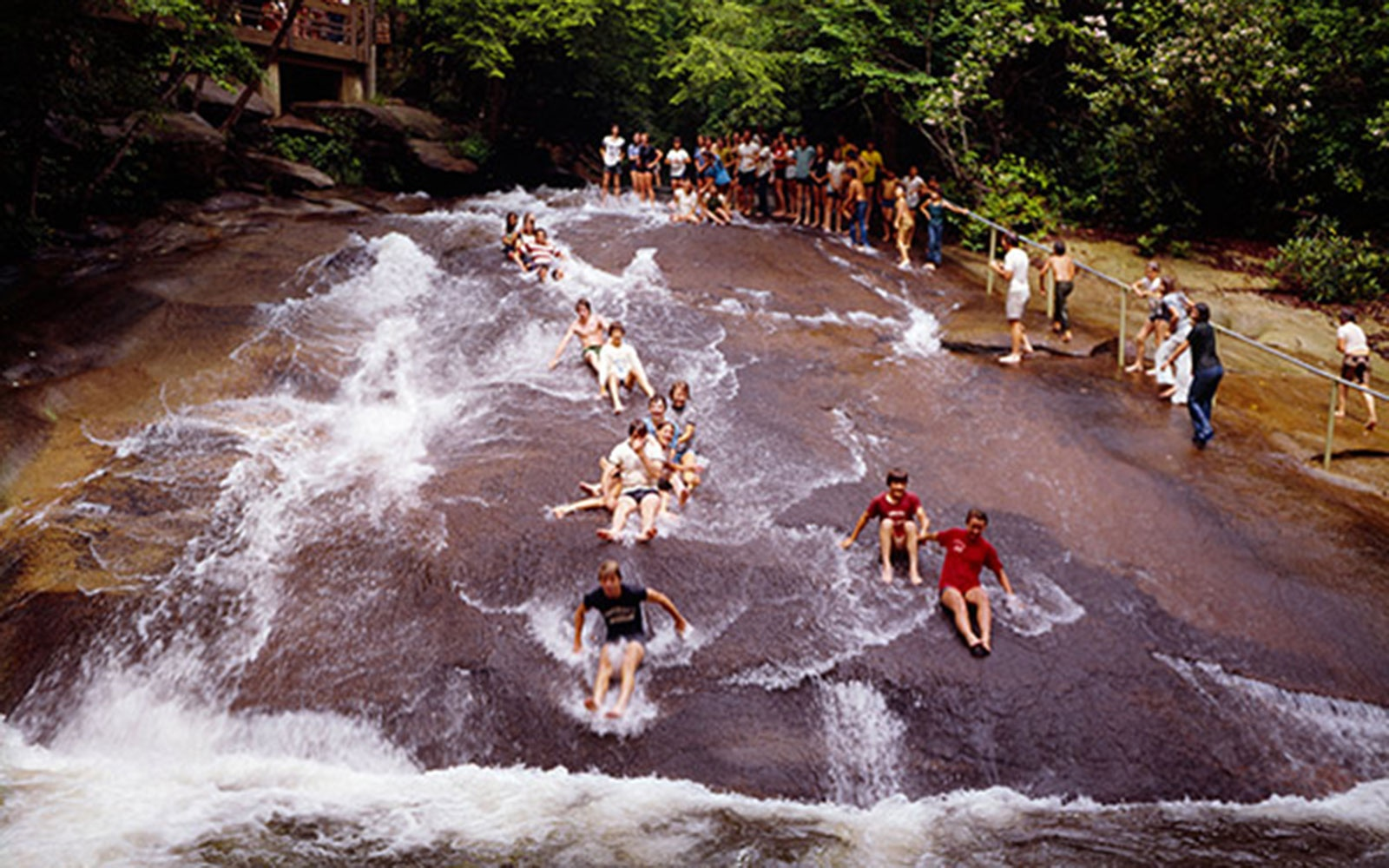 pool swimmers sliding down Sliding Rock in Brevard, NC