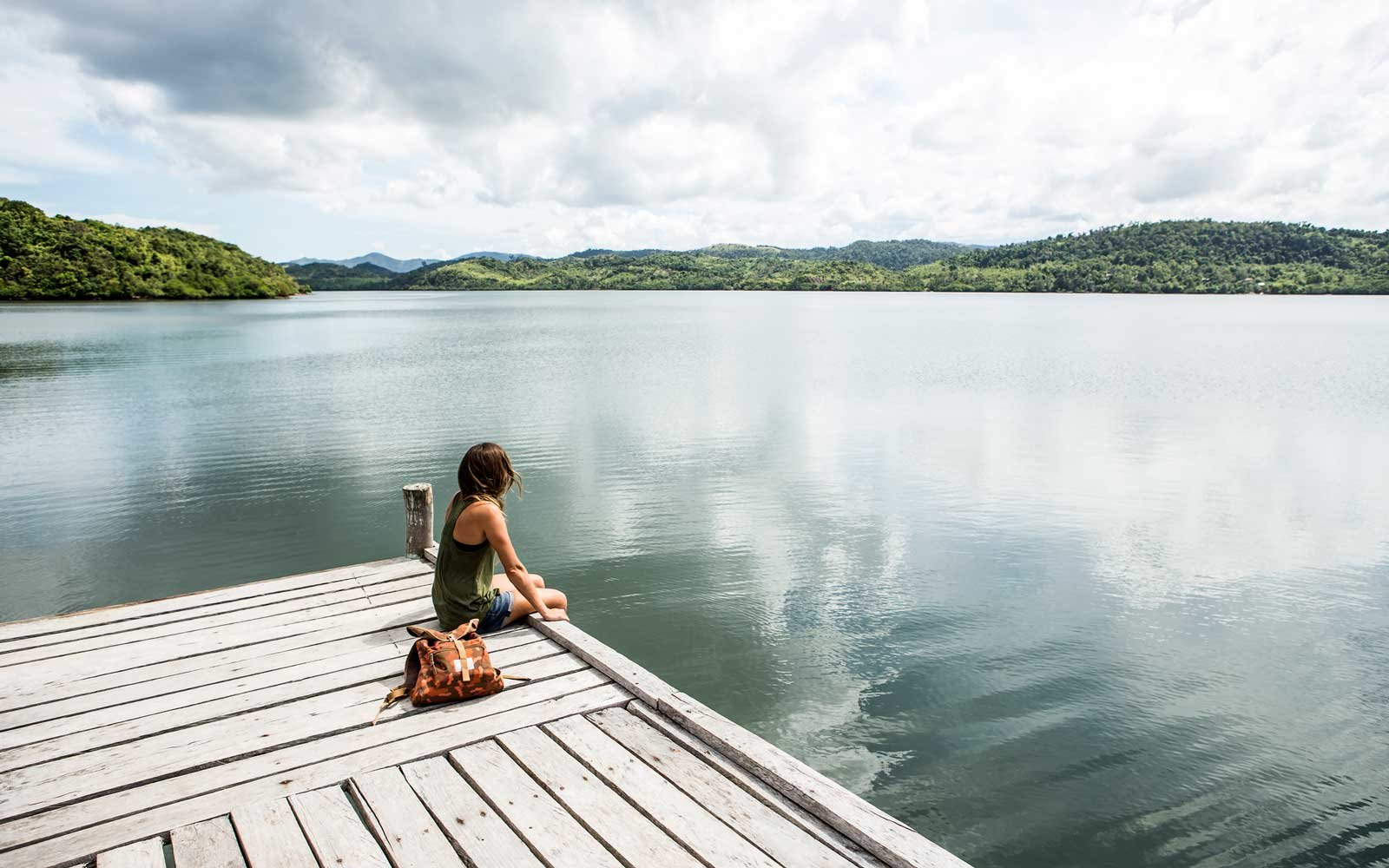 A woman sitting on a remote wooden dock overlooking a lake.