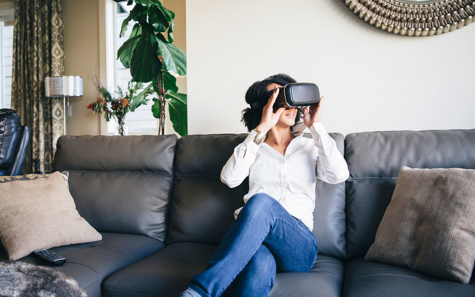 Woman sits on a couch wearing a VR headset.