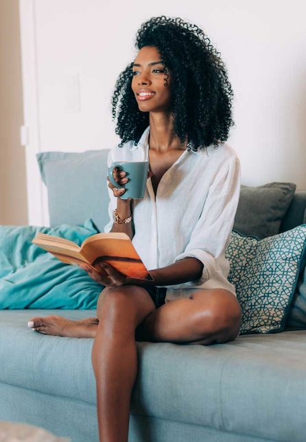 Young woman reading a book at home while drinking coffee