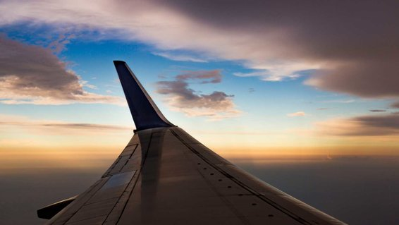 View of an Airplane Wing in Flight at Sunset with Winglets