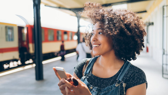 Instagram travel hashtags: A woman looks at Instagram on her phone while traveling
