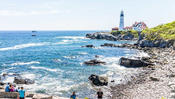 People sitting on cliff rocks looking at Portland Head Lighthouse in Fort Williams park in Maine during summer day